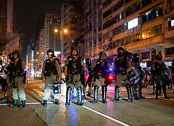 Hong Kong, China. 13th October 2019. Woman suspected of being pro-Beijing is assaulted by pro-democracy protestors in Mongkok district in Kowloon on Sunday evening. This incident was one of several throughout Hong Kong on Sunday which saw acts of vandalism carried out by a minority in the pro-democracy movement. Riot police on Nathan Road in Kowloon. Iain Masterton/Alamy Live News.