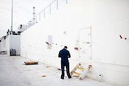 A sailor checks his phone on board the USNS Comfort, a naval hospital ship, before it gets under way to Haiti to assist earthquake victims on Saturday, January 16, 2010 in Baltimore, MD.