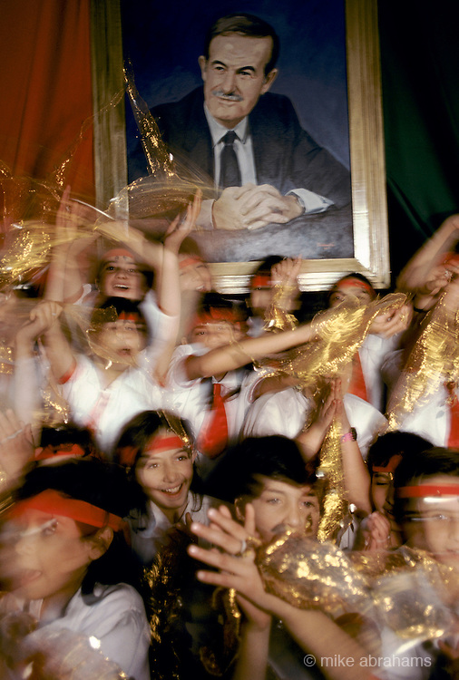 'PERSONALITY CULT OF ASSAD', CHILDREN CELEBRATING WITH GOLD MATERIAL IN FRONT OF PORTRAIT OF ASSAD, DURING THE REFERENDUM CAMPAIGN, DAMASCUS, DECEMBER 1991