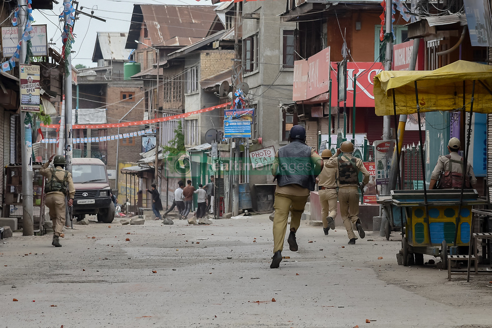 May 13, 2019 - Srinagar, Jammu and Kashmir, India - Indian forces are seen chasing Kashmiri Protesters during the protest in Srinagar..Indian forces in Srinagar fired pellets and tear gas smoke canisters to disperse Protesters, who were demonstrating against the alleged rape of three year old girl from north Kashmir Bandipora. (Credit Image: © Idrees Abbas/SOPA Images via ZUMA Wire)