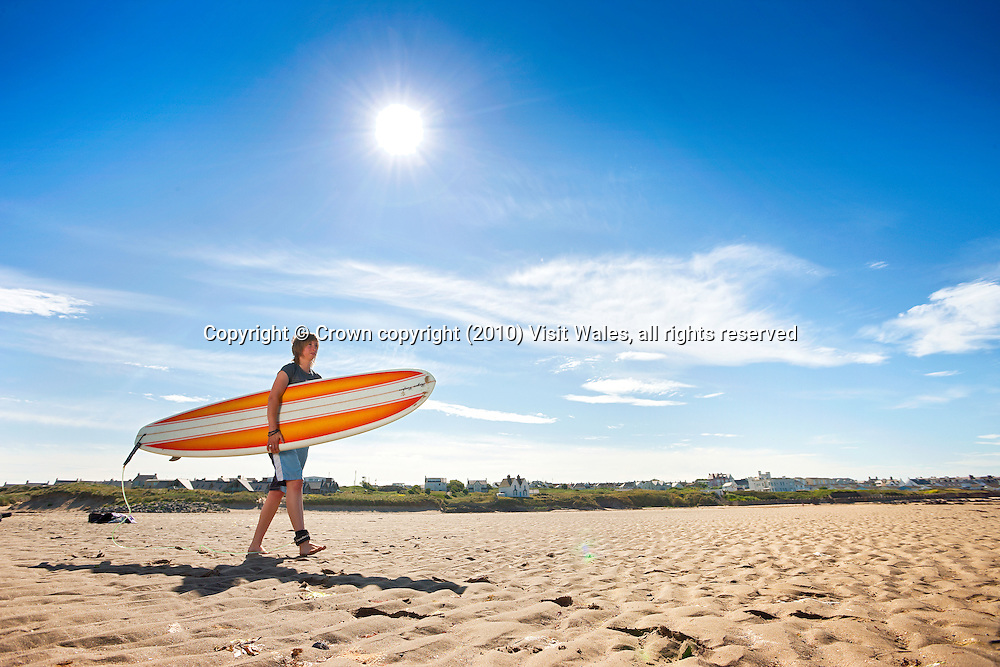 Woman carrying surfboard on beach<br /> Surfing<br /> Rhosneigr<br /> Anglesey<br /> North<br /> Activities And Sports