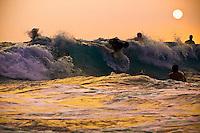 Riders catch last waves on June evening at Magic Sands Beach, in Kona, HI.  Copyright 2009 Reid McNally.