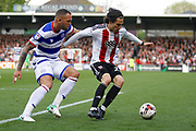 Queens Park Rangers defender Joel Lynch (6) is held off by Brentford midfielder Jota (23) during the EFL Sky Bet Championship match between Brentford and Queens Park Rangers at Griffin Park, London, England on 22 April 2017. Photo by Andy Walter.