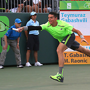 Milos Raonic of Canada reaches for the ball during his match against Teymuraz Gabashvili of Russia at the Miami Open tennis tournament on Saturday, March 28, 2015 in Key Biscayne, Florida. (AP Photo/Alex Menendez)