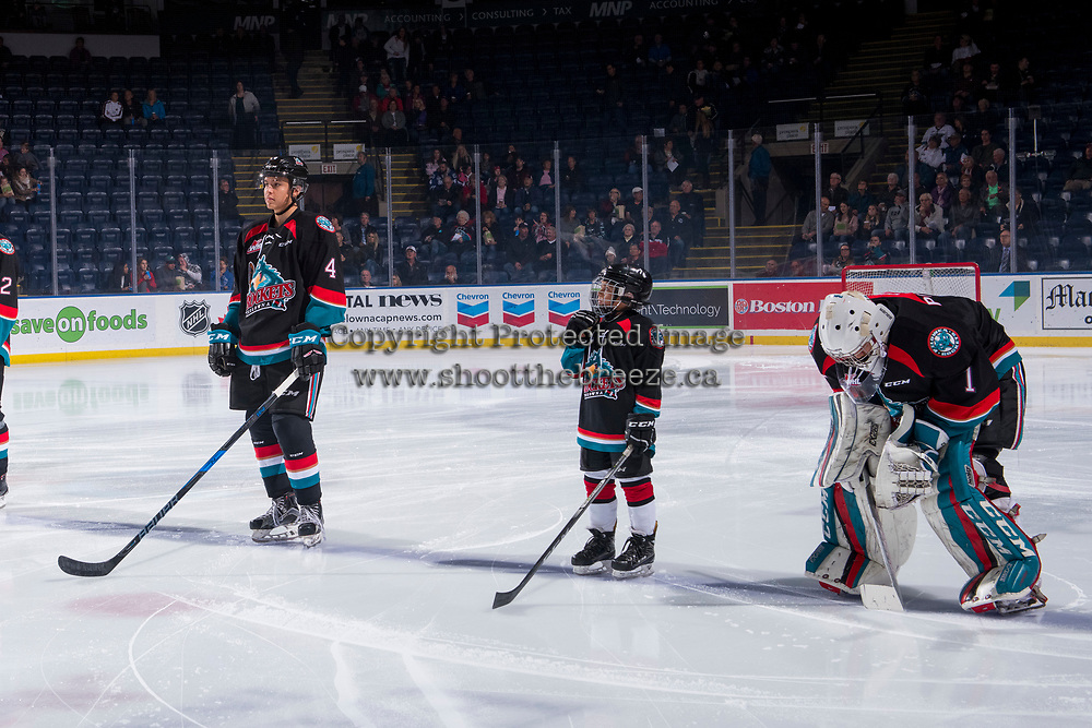 KELOWNA, CANADA - OCTOBER 5: The Save-On Foods player of the game lines up on the blue line between Devin Steffler #4 and  James Porter #1 of the Kelowna Rockets against the Victoria Royals  on October 5, 2018 at Prospera Place in Kelowna, British Columbia, Canada.  (Photo by Marissa Baecker/Shoot the Breeze)  *** Local Caption ***