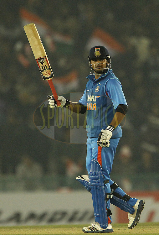 Suresh Raina of India raises his bat to celebrate his fifty during the 4th Airtel ODI Match between India and England held at the PCA Stadium, Mohal, India on the 23rd January 2013..Photo by Ron Gaunt/BCCI/SPORTZPICS ..Use of this image is subject to the terms and conditions as outlined by the BCCI. These terms can be found by following this link:..http://www.sportzpics.co.za/image/I0000SoRagM2cIEc