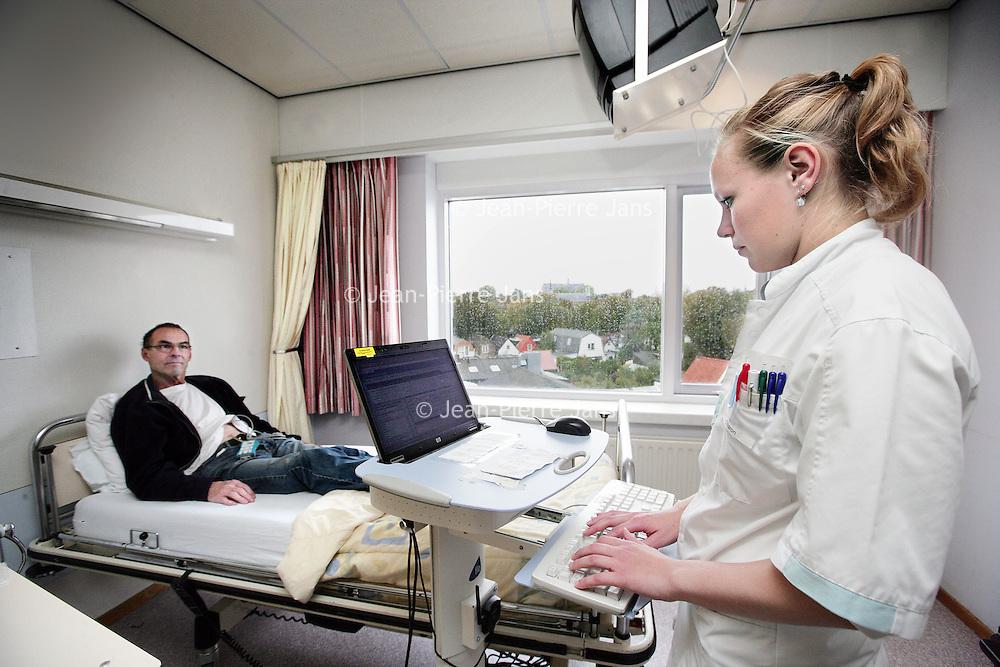 Nederland, Alkmaar , 7 oktober 2009. .Het Medisch Centrum Alkmaar (MCA) neemt vanaf september als eerste ziekenhuis in Noord-Holland 24 uur per dag patiënten op die een TIA hebben gehad..Bij een TIA (Transient Ischaemic Attack) krijgt een deel van de hersenen tijdelijk te weinig bloed, waardoor sommige hersencellen een moment minder goed of helemaal niet werken..Volgens MCA-neuroloog Majid Aramideh is het heel belangrijk dat patiënten direct de huisarts bellen wanneer zich uitvalsverschijnselen voordoen..Op de foto wordt een TIA patient via een computer die weer via een apparatje op het lichaam van de patient nauwlettend in de gaten houd of er  eventuele hartritme storingen voorkomen. .24 hours a day the Medical Center Alkmaar (MCA) is the first hospital is taking in  patients who have had a TIA.