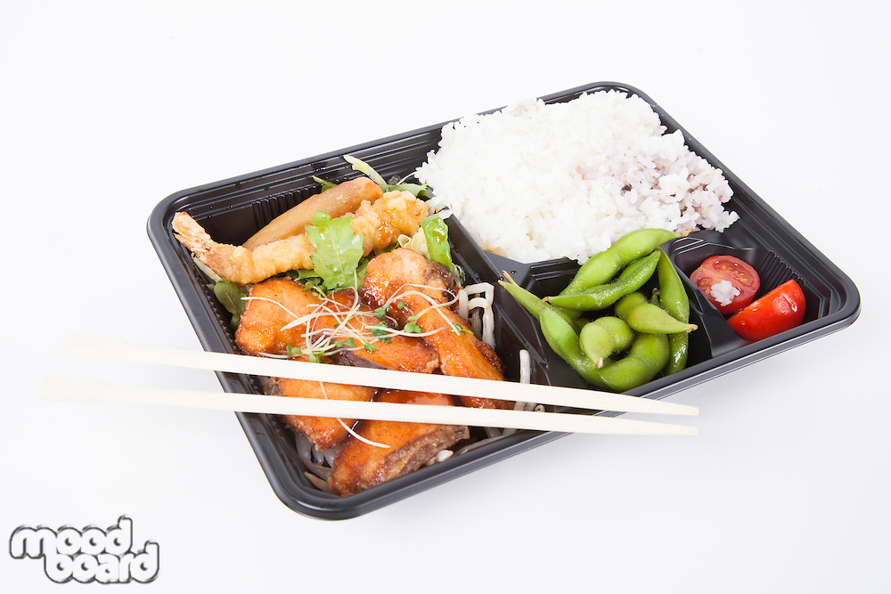 Healthy food served in tray with chopsticks over white background