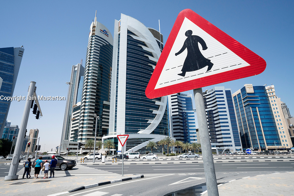 View of modern office towers and road crossing sign  in West Bay financial and business district in Doha Qatar