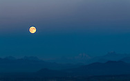 The moon rises into the Earth's Shadow over the peaks of the North Cascades mountains in Washington State, USA.  Peaks here include (L to R) Round Mountain, Mount Higgins, Skadulgwas Peak, White Chuck Mountain, Glacier Peak, Disappointment Peak and Whitehorse Mountain.  Photographed from Mt. Erie Park on Fidalgo Island, Washington.
