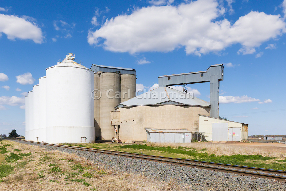 Grain silo rail transport depot in Macalister under blue sky in rural country Queensland, Australia. <br /> <br /> Editions:- Open Edition Print / Stock Image