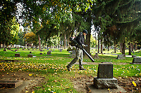 Nick Goodwin, with the City if Coeur d'Alene, clears leaves and pine needles Wednesday from the headstones at Forest Cemetery.