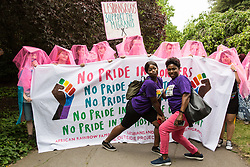 London, UK. 6 July, 2019. Activists from Lesbians and Gays Support The Migrants and African Rainbow Family prepare to take part in a London Pride Solidarity March at the very rear of Pride in London - stewards tried to prevent them from joining - in solidarity with those for whom Pride in London is inaccessible and in protest against the corporatisation of Pride in London.