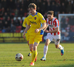 Cheltenham Town's Wes Burns attempts a challenge against Exeter City's Christian Ribeiro -Photo mandatory by-line: Nizaam Jones - Mobile: 07966 386802 - 21/03/2015 - SPORT - Football - Cheltenham - Whaddon Road - Cheltenham Town v Exeter City - Sky Bet League Two
