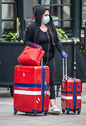 © Licensed to London News Pictures. 19/03/2020. London, UK. A women in a mask with suitcases and rucksacks at London Victoria Bus Station as London prepares to shutdown over the Coronavirus pandemic crisis. Photo credit: Alex Lentati/LNP