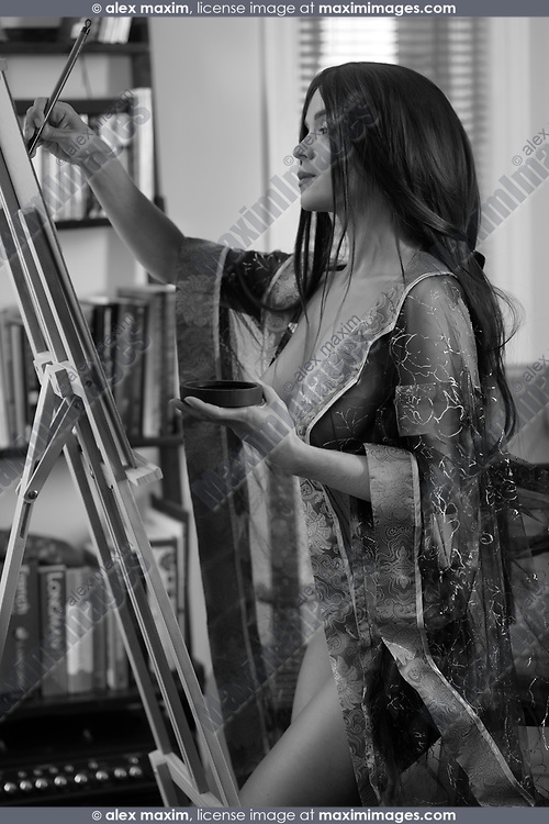 Black and white portrait fo a beautiful young woman sumi-e artist with an easel painting half nude in comfort of her home studio wearing just a light see-thorugh robe over her naked body
