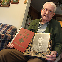 RAY VAN DUSEN/BUY AT PHOTOS.MONROECOUNTYJOURNAL.COM<br /> Buford Easter, who turned 100 on Jan. 18, holds a picture from his Army years and a yearbook of the 4th Infantry Division from World War II in his Aberdeen home.