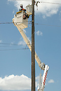 Electric company linesman replacing a fuse on a high-power line.
