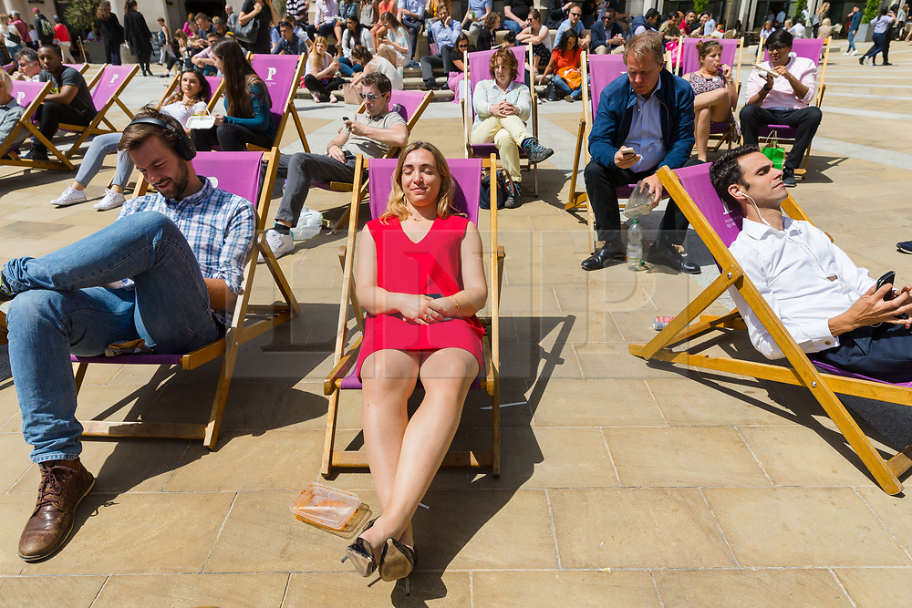 © Licensed to London News Pictures. 28/06/2019. London, UK.  Office workers and tourists relax in deckchairs at lunchtime during the warm and sunny weather near St Paul's Cathedral in London on Friday lunchtime. A heatwave is forecast across much of the UK tomorrow, with temperatures in the capital expected to reach 33 degrees celcius.  Photo credit: Vickie Flores/LNP