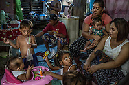 """Three generations of the Dela Cruz family in their house raised on post above a contaminated swamp in Bagung Bayan, C4 in Navotas.  Son, John """"Toto"""" Dela Cruz, 16, was gunned down on the porch of their home leaving behind his 15 year old widow, Jasmin Dorana, 15, and a baby daughter, Hazel, held by Toto's mother (R).  Metro Manila, Philippines"""