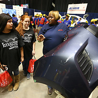 Adam Robison | BUY AT PHOTOS.DJOURNAL.COM<br /> Maggie Walker, right, a team member in Bumper and Paint at Auto Parts Manufacturing Mississippi, describes the steps of building the bumpers for the Toyota Corolla, to Itawamba Attendance Center students Laken Rollins, 14, and Selena Crowley, at 2nd annual Imagine the Possibilites Career Expo Tuesday morning in Tupelo.
