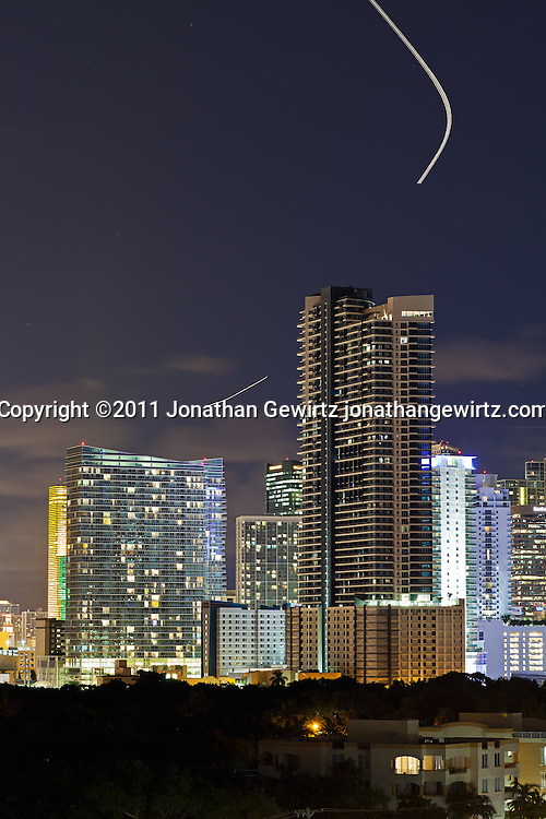Downtown Miami, Florida office and residential buildings at night with aircraft trails. WATERMARKS WILL NOT APPEAR ON PRINTS OR LICENSED IMAGES.