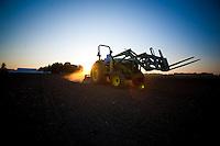 Farmer drives John Deere Tractor at sunrise on organic farm in Oregon.