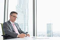 Mature businessman text messaging through cell phone near office window