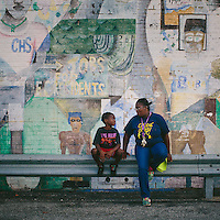 East Chicago, Indiana<br /> <br /> Nayesa Walker and her 7-year-old son Kash Lott wait for a school bus to drop off his two younger siblings at the West Calumet Housing Complex. As a child, Walker helped create the mural that covers the neighborhood's community center. Walker and other residents tried to stop the neighborhood's demolition. &quot;We feel like we're just being thrown out,&quot; Walker said.<br /> <br /> ||||<br /> <br /> The West Calumet Housing Complex, which is currently home to about 1,200 people, is located on a 79-acre Environmental Protection Agency Superfund site where a USS Lead facility was located in East Chicago, Indiana. Up until 1985, a lead refinery, a copper smelter and a secondary lead smelter were also in the area. The houses were built between the late 1960s and early 1970s.<br /> <br /> East Chicago is zoned close to 80 percent heavy industrial, and the local government relies on the patronage, jobs and tax revenue that the oil and steel industries bring. However, many jobs disappeared when the steel industry modernized and shifted overseas in the late 20th century, leading to extensive job loss for the working class. People there have a long, complicated relationship with industry -- and its environmental legacy will affect generations to come.<br /> <br /> Photo by Alyssa Schukar