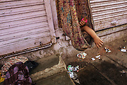 Dharavi, the second largest slum in Asia, wedged between Mumbai's two railways and under a string of power pylons. A child sleeping in a sari.