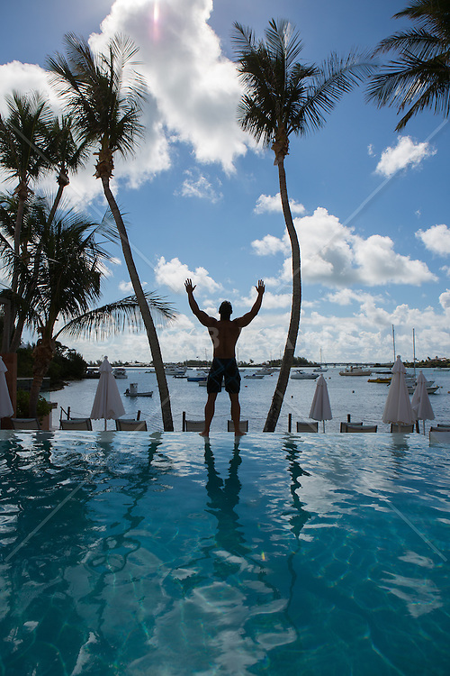 man standing by a swimming pool in Bermuda against the sky