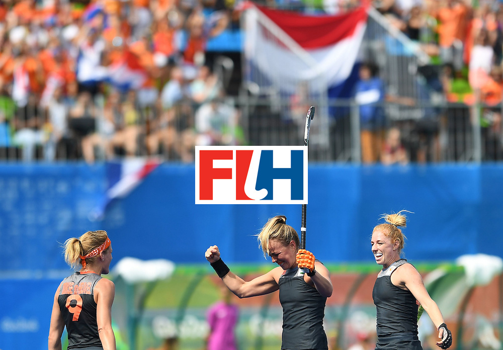 Netherland's Maartje Paumen (C) celebrates scoring a goal with teammates Carlien Dirkse van den Heuvel (L) and Caia van Maasakker during the women's field hockey Netherlands vs Spain match of the Rio 2016 Olympics Games at the Olympic Hockey Centre in Rio de Janeiro on August, 7 2016. / AFP / MANAN VATSYAYANA        (Photo credit should read MANAN VATSYAYANA/AFP/Getty Images)
