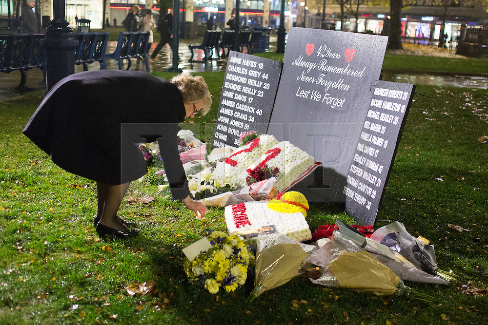 © Licensed to London News Pictures. 21/11/2016. Birmingham, UK. A service of prayer to mark the deaths of 21 people killed in the Birmingham Pub bombings on the 42nd anniversary. Pictured, Julie Hamilton lays a candle on behalf of her sister. credit: Dave Warren/LNP