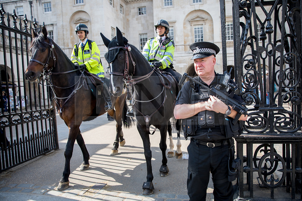 © Licensed to London News Pictures. 28/03/2017. London, UK. Armed police stand at the entrance to Horseguards Parade, as four police horses patrol around Whitehall. Security around London has been increased following Khalid Masood's terrorist attack and the killing of PC Keith Palmer on 22 March. Photo credit : Tom Nicholson/LNP