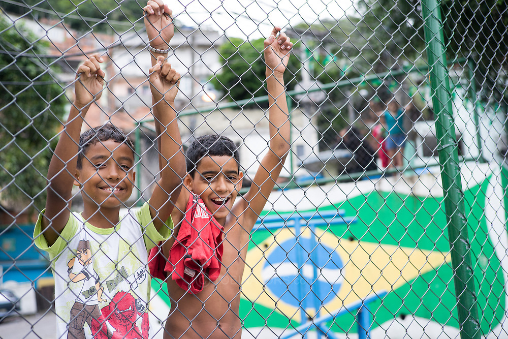 Two young boys pose for a photograph behind the chain link fence surrounding a concrete football pitch in the Santo Amaro favela, Rio de Janeiro, Brazil. The favela has not been pacified and is one of the less well known of Rio's favelas. A heavily armed police presence was inevidence and there was no trouble of any sort while we were there. According to our guide, Patrick Ashcroft, a teacher and research worker who lives in the favela, violence is rare in this favela. Photo by Andrew Tobin/Tobinators Ltd