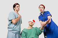 Male doctor with female nurse treating an injured patient against gray background