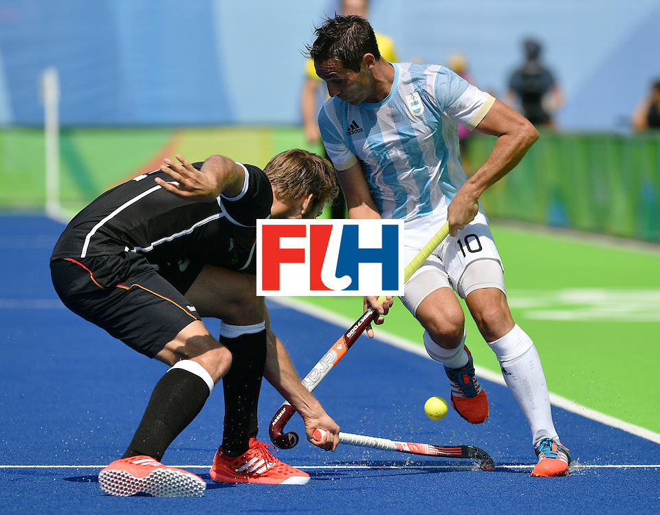 Argentina's Matias Paredes (R) vies with Germany's Moritz Furste during the men's semifinal field hockey Argentina vs Germany match of the Rio 2016 Olympics Games at the Olympic Hockey Centre in Rio de Janeiro on August 16, 2016. / AFP / Pascal GUYOT        (Photo credit should read PASCAL GUYOT/AFP/Getty Images)