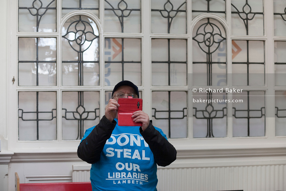 A protester records the interior of the re-opened Carnegie Library on Herne Hill in south London which has opened its doors for the first time in almost 2 years, on 15th February 2018, in London, England. Closed by Lambeth council and occupied by protesters for 10 days in 2016, the library bequeathed by US philanthropist Andrew Carnegie has been locked ever since because, say Lambeth austerity cuts are necessary. A gym that locals say they don't want or need has been installed in the listed basement and actual library space a fraction as before and it's believed no qualified librarians will be present to administer it. Protesters also believe this community building will ultimately sold off by Lambeth council for luxury homes.