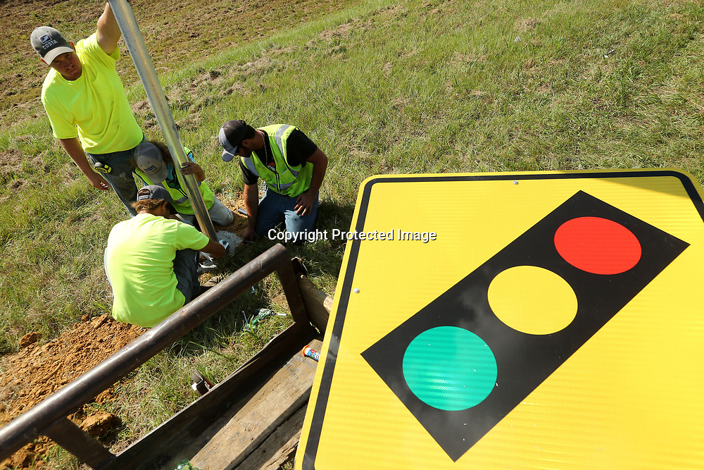 MDOT workers install one of two new redlight signs on the north bound lane of highway 45 just south of the Ripley Road intersection on Thursday morning. MDOT is making improvements to signage at more than 100 intersections across the district, focusing on the more dangerous one.