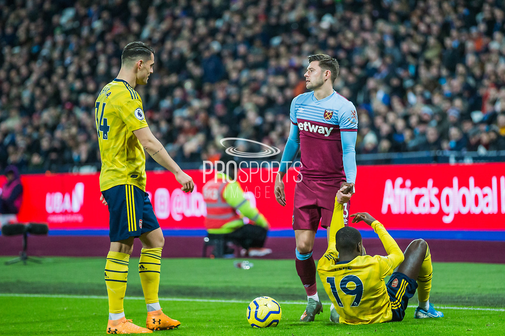 Aaron Cresswell (West Ham) helping up Nicolas Pepe (Arsenal) during the Premier League match between West Ham United and Arsenal at the London Stadium, London, England on 9 December 2019.