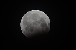 August 8, 2017 - Lahore, Punjab, Pakistan - A view of second lunar eclipse of the year in Lahore on August 07, 2017. A partial lunar eclipse occurs when a portion of moon passes through Earth's umbra shadow. Depending on the size of the eclipse, a dark red or rust color or simply a charcoal grey may appear on the shadowed portion of the lunar surface. (Credit Image: © Rana Sajid Hussain/Pacific Press via ZUMA Wire)