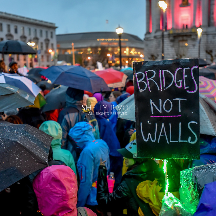 "Marchers in umbrellas and rain coats make slow progress from City Hall toward Market Street.  A sign reads, ""Bridges not walls."""