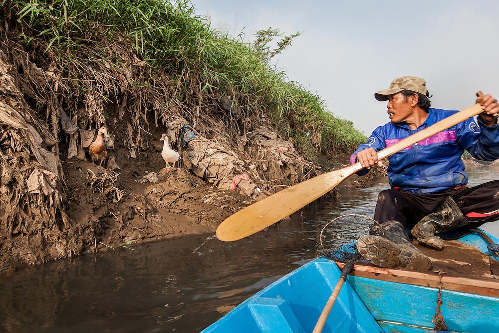 Abah Dayat looks for scraps on the Citarum River. Citeureup Village, Kabupaten Bandung...Credit: Andri Tambunan for Greenpeace