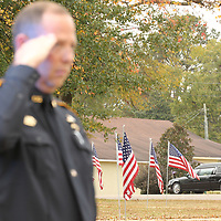 The funeral procession for former Bruce Police Chief Stanley Evans makes past variuos law enforcement officers and American flags surrounding downtown Bruce Saturday.