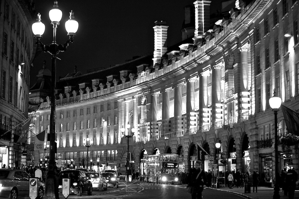 Night view of Regent street in London, Great Britain. Black and white photograph highlights architectural details and lights of city centre.