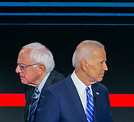 Democratic presidential candidate Sen. Bernie Sanders (I-VT) walks past former Vice President Joe Biden during a commercial break of the first primary debate for the 2020 elections at the Adrienne Arsht Center for the Performing Arts in downtown Miami on Thursday, June 27, 2019.