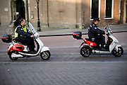 In Utrecht rijden twee medewerkers van de dienst handhaving op een elektrisch aangedreven scooter door de binnenstad.<br /> <br /> In Utrecht two members of the enforcement department of the municipal of Utrecht ride on a electrical scooter.