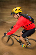 A mountain bikers steers through a tight corner while heading downhill on a dirt trail in Hail Ranch near Boulder, Colorado.