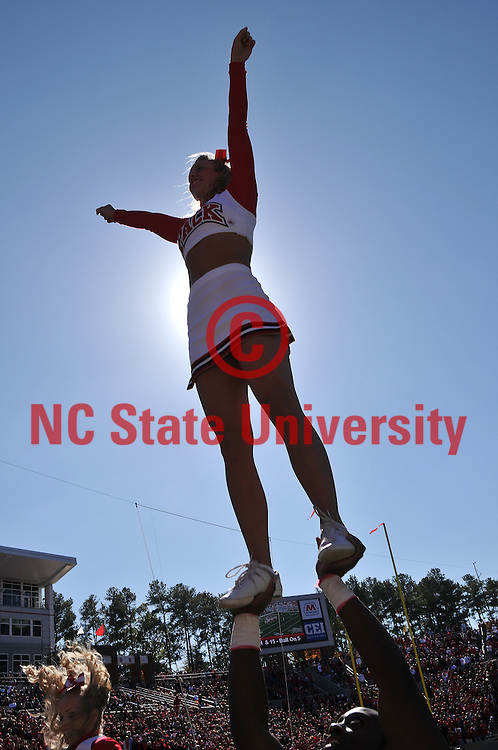 Wolfpack cheerleader leads fans in a cheer.
