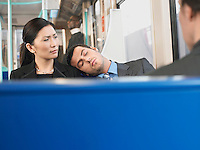 Man Sleeping on Businesswoman's Shoulder on Train